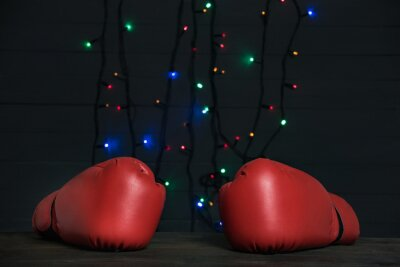 Pair of red boxing gloves, festive garland on background. Boxing day