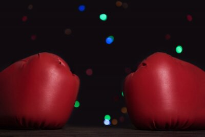 Pair of red boxing gloves, festive garland on background. Close up
