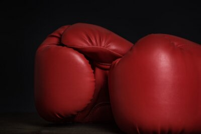 Pair of red boxing gloves on a black background. Close up