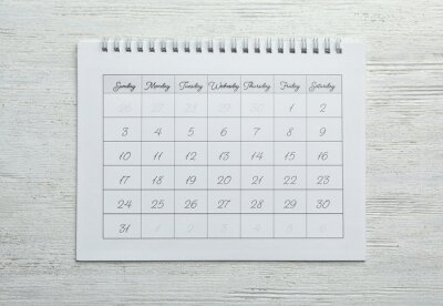 Bild Paper calendar on white wooden background, top view
