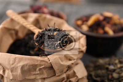 Bild Papiertüte und Löffel mit trockenen schwarzen Teeblättern auf dem Tisch