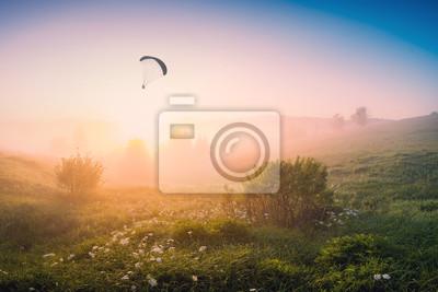Paraglide-Silhouette fliegen am frühen Morgen