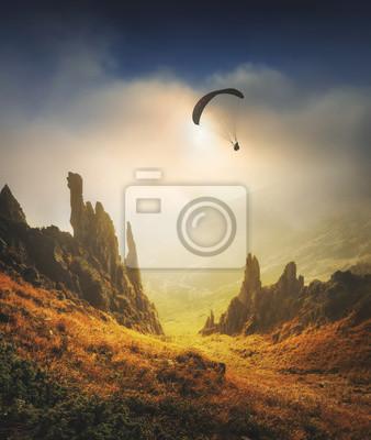 Paraglide Silhouette fliegen über das Bergtal