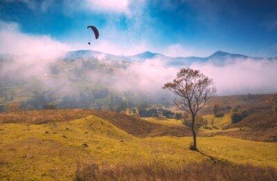 Paraglide Silhouette fliegen über nebligen Karpaten Hügel