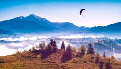 Paraglider silhouette flying above misty carpathian hills