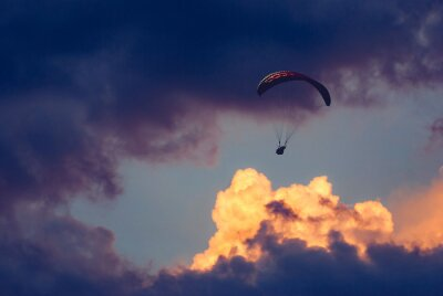 Paraglider silhouette flying in a cloudy sky