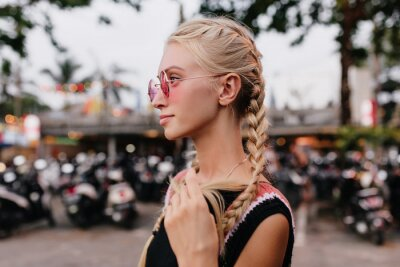 Bild Pensive blonde woman in black attire posing on blur street background. Outdoor shot of serious tanned lady with braids wears pink sunglasses.