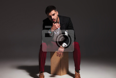 Bild pensive young attractive man sitting on wood box