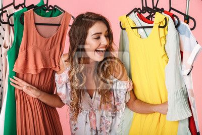 Bild Photo of attractive woman in dress standing inside wardrobe rack full of clothes