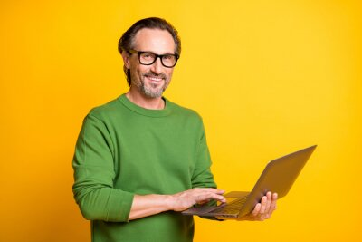 Bild Photo of man hold netbook hand touch pad wear eyewear green sweater isolated yellow color background