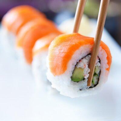Bild picking up a piece of sushi with chopsticks