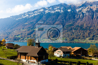 Bild Picturesque alpine meadows, chalets, lake and church with a clocktower in the Swiss Alps