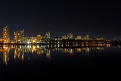 Bild picturesque dark cityscape with illuminated buildings, river and night sky