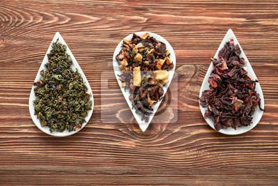 Bild Platten mit Vielzahl von trockenen Teeblättern auf hölzernem Hintergrund