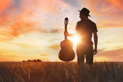 Bild play music, silhouette of musician with guitar at sunset field outside