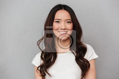 Bild Portrait der asiatischen reizenden Frau mit dem dunklen lockigen Haar, das mit dem netten Lächeln, getrennt über grauem Hintergrund aufwirft