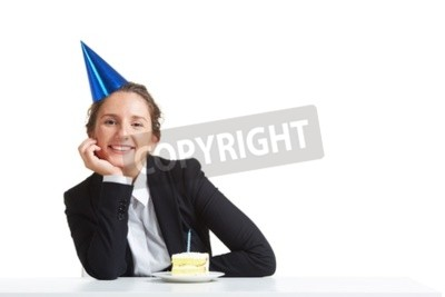 Bild Portrait der jungen Geschäftsfrau in der Geburtstagschutzkappe, die Kamera mit Stück Kuchen vor ihr