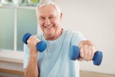 Portrait des älteren Mannes, der mit Dumbbells trainiert