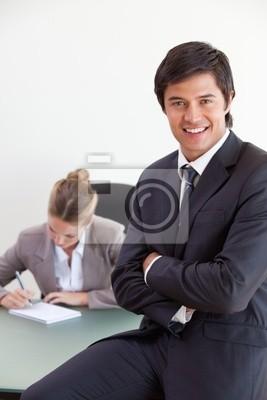 Portrait eines Büroangestellten posieren, während sein Kollege Arbei