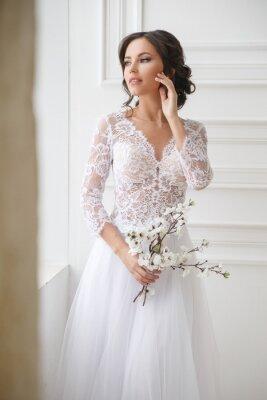 Bild Portrait of a beautiful elegant bride with a bouquet of sakura in a bright interior.