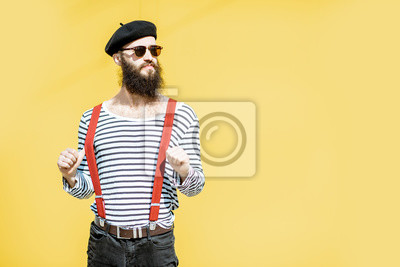 Bild Portrait of a stylish bearded man dressed in striped shirt, suspenders and hat on the yellow background outdoors