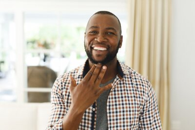 Bild Portrait of african american man smiling and looking at camera in living room talking sign language