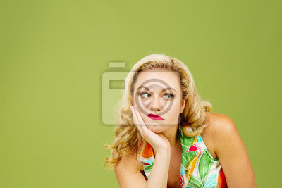 Bild Portrait of an envious woman in bad mood looking right, isolated on green studio background