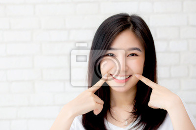 Bild Portrait of beautiful young asian woman happiness standing finger touch cheek on gray cement texture grunge wall brick background, businesswoman is a smiling on concrete, business people concept.