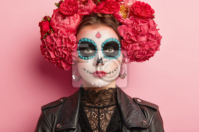 Bild Portrait of calm female celebrates Day of Death, has sugar skull makeup, dark circles near eyes, painted smile, thinks death is natural part of human cycle, wears traditional mexican attire.