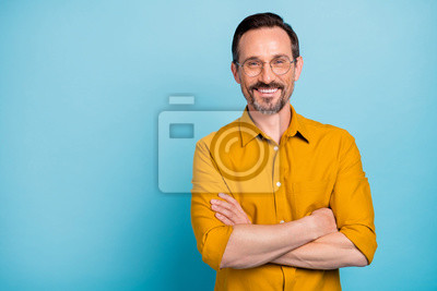 Bild Portrait of charming mature man true boss feel content emotions wear yellow shirt isolated over blue color background