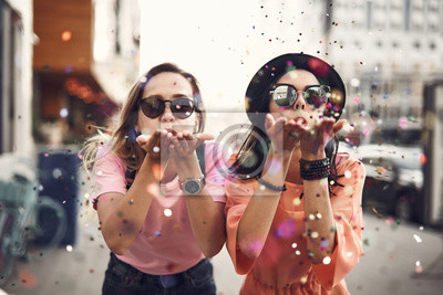 Bild Portrait of cheerful ladies blowing confetti from hands. They situating on street during sunny day. Glad girl having fun, celebration concept