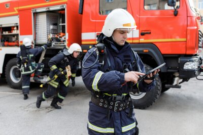Bild Portrait of firefighter in fire fighting operation, fireman in protective clothing and helmet using tablet computer in action fighting.