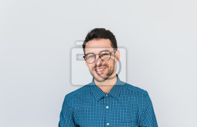 Bild Portrait of handsome smart-looking smiling male posing for social advertisement wearing blue shirt and glasses, isolated on white background with copy space for your promotional information or content