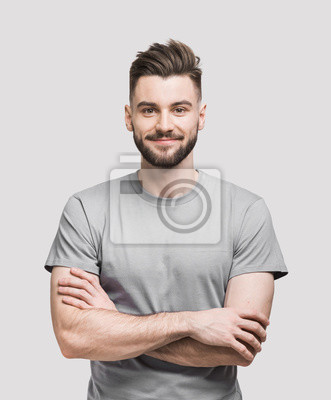 Bild Portrait of handsome smiling young man with folded arms. Smiling joyful cheerful men with crossed hands studio shot. Isolated on gray background