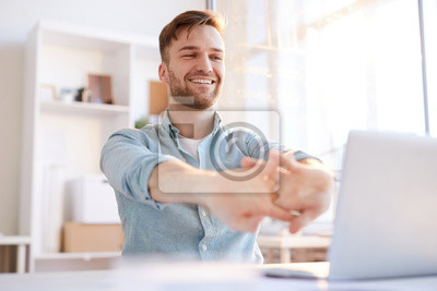 Bild Portrait of handsome young man  stretching at workplace in office and smiling happily, copy space