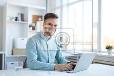 Bild Portrait of handsome young man working in office and smiling happily at camera, copy space