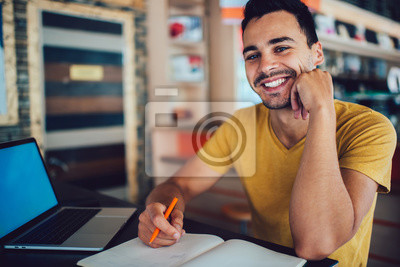 Bild Portrait of happy hipster guy looking at camera and smiling while sitting at desktop with laptop computer for e learning and textbook for knowledge education, cheerful male student feeling good