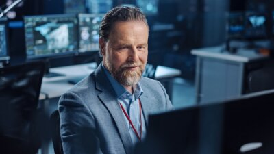 Bild Portrait of Positive Professional Technical Controller Sitting at His Desk with Multiple Computer Displays Before Him. In the Background His Colleagues Working in System Control and Monitoring Center.