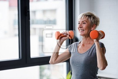 Bild Portrait of senior woman lifting dumbbells