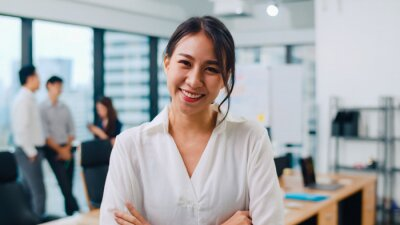 Bild Portrait of successful beautiful executive businesswoman smart casual wear looking at camera and smile, arms crossed in modern office workplace. Young Asia lady standing in contemporary meeting room.