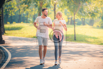 Bild Portrait of Young couple running in the park at sunset. Concept sport and love. Warm tone.
