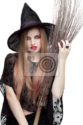 Portrait of young woman in witch costume with a broom