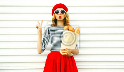 Bild Portrait pretty cool girl wearing french red beret holding paper bag with long white bread baguette on white wall background