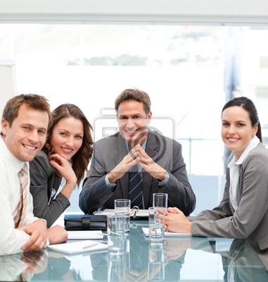 Porträt eines positiven Managers mit seinem Team an einem Tisch sitzen