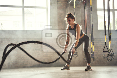 Bild Preparing for the competition. Young athletic woman with perfect body doing crossfit exercises with a rope in the gym.