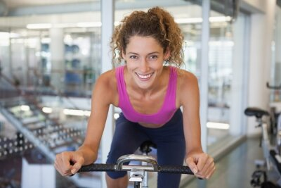 Pretty fit woman on the spin bike smiling at camera