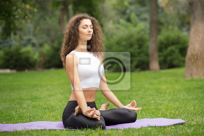 Pretty woman doing yoga meditation in the lotus position