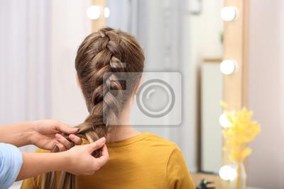 Bild Professional coiffeuse braiding client's hair in salon