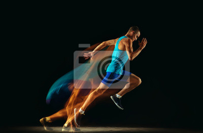 Bild Professional male runner training isolated on black studio background in mixed light. Man in sportsuit practicing in run or jogging. Healthy lifestyle, sport, workout, motion and action concept.