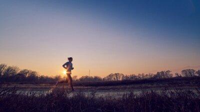 Bild Ragazza atletica si allena all'aperto su terra di sera